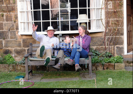 grandfather and grandchildren celebrating the grandfather's speedy time in a garden obstacle competition - Stock Photo