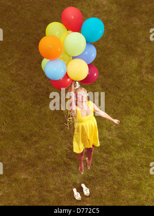 Happy young woman in yellow summer dress flying up from the ground with colorful helium balloons, retro stylized - Stock Photo
