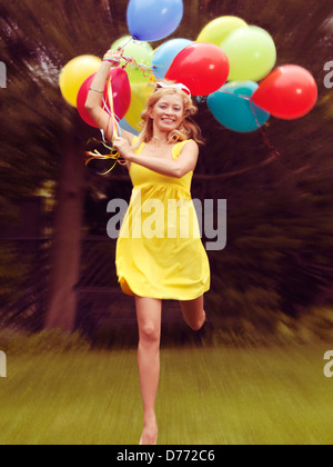 Happy young woman in summer dress running with colorful balloons - Stock Photo