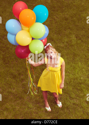 Young smiling woman standing on grass with a bunch of colorful helium balloons in her hand. Retro stylized image. - Stock Photo