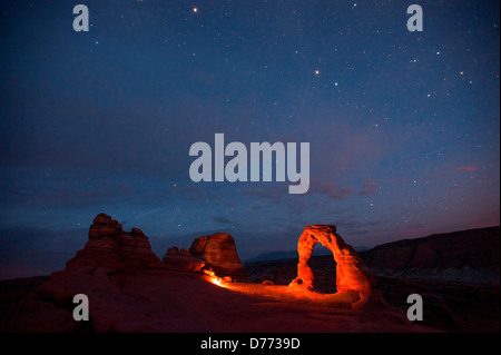 The star filled night sky seen over Delicate Arch night in Arches National Park Utah where person used torch or - Stock Photo