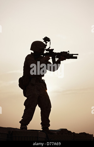 Silhouette U.S. Marine Aiming M4 Carbine During Combat Operation in Afghanistan's Helmand Province - Stock Photo
