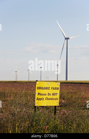 Organic Farm Sign Alerting Against Spraying Chemicals Distant Wind Turbines - Stock Photo