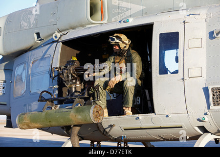 United States Marine gunner aboard UH-1Y Venom helicopter just prior to launching on combat operation in Helmand - Stock Photo