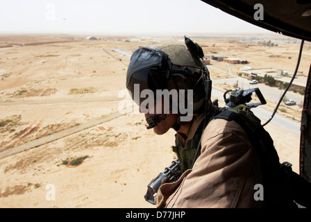 US Marine flight crew chief scans desert below Marine Corps UH-1N utility helicopter fitted weapons during combat - Stock Photo