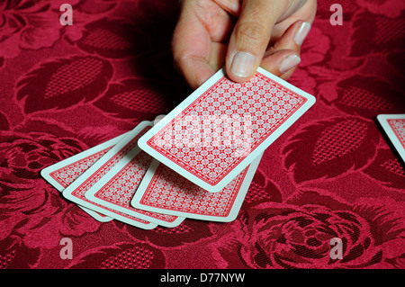 Woman dealing a pack of playing cards against a red background. - Stock Photo