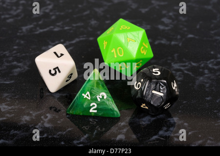 Platonic dice selection against a black background. - Stock Photo