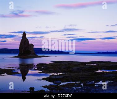 Pastel light sunset silhouetting sea stack tide pools along shore Nunavachak Bay Togiak National Wildlife Refuge - Stock Photo