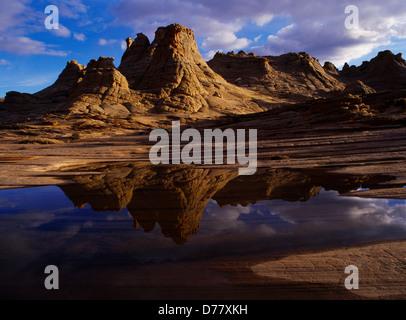 Navajo Sandstone beehives reflected in ephemeral slickrock pool Colorado Plateau in northern Arizona. - Stock Photo