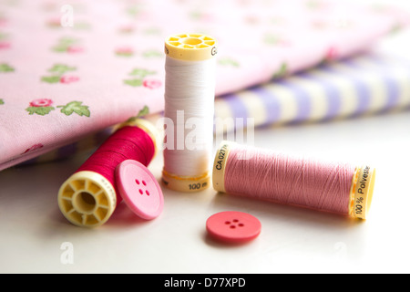 Sewing accessories - thread, fabric and buttons placed on a light grey background