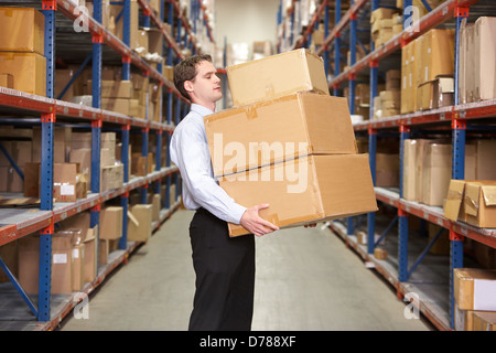 Man Carrying Boxes In Warehouse - Stock Photo
