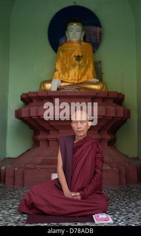 Ein buddhistischer Mönch sitzt am 30.03.2013 an der Shwedagon-Pagode in Rangun, Myanmar, vor einer Buddha Figur. - Stock Photo