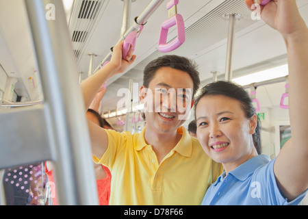 Adult couple standing in the subway and smiling, portrait - Stock Photo
