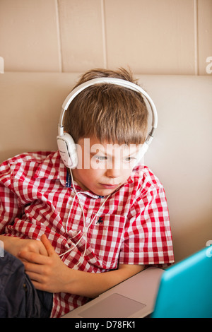 boy using laptop and headphones - Stock Photo