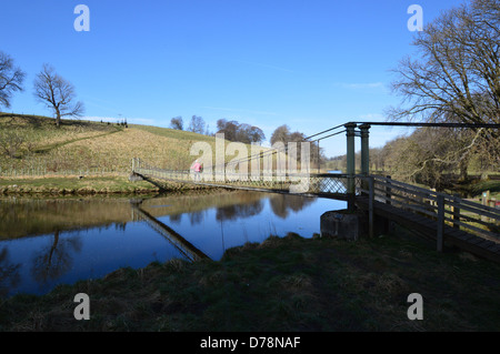 Woman Walking Across the Suspension Bridge over the River  Wharfe near Hebden on the Dales Way Long Distance Footpath - Stock Photo