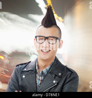 Young man with punk Mohawk smiling - Stock Photo