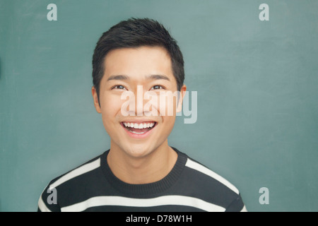 Portrait of smiling, happy young man in front of blackboard - Stock Photo