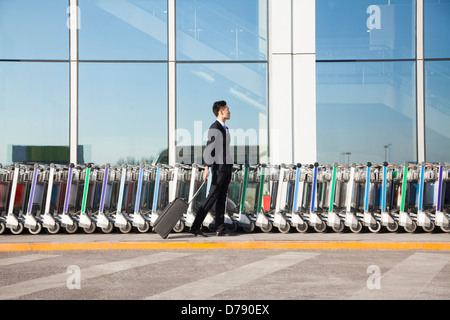 Traveler with suitcase next to row of luggage carts at airport - Stock Photo