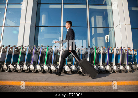 Traveler walking fast next to row of luggage carts at airport - Stock Photo