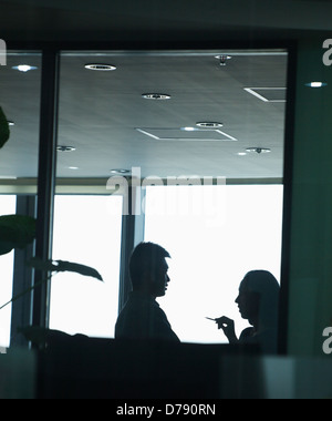 Two co-workers talking in office - Stock Photo
