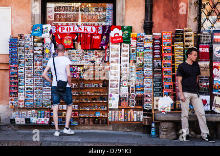 A tourist looks at a postcard and souvenir stall in Stary Rynek, Old Town Market Place in Warsaw, Poland. - Stock Photo