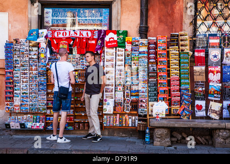 A tourist talks with the owner of a postcard and souvenir stall in Stary Rynek, Old Town Market Place in Warsaw, - Stock Photo