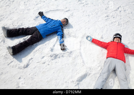 Couple Lying On Snow Making Snow Angel - Stock Photo