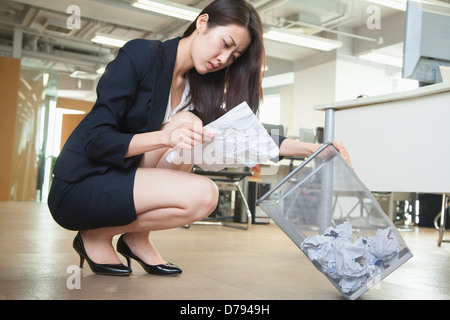 Young businesswoman reading piece of paper from the trash can in office - Stock Photo