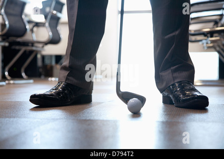 Businessman playing golf in his office, close up on feet - Stock Photo