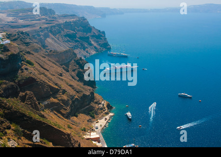 Caldera view on island of Santorini, Greece in Aegean sea with big and small commercial passenger ships - Stock Photo