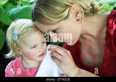Mother dries the tears of her toddler daughter. - Stock Photo