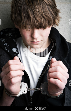 teen male portrait wearing handcuffs - Stock Photo