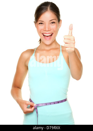 weight loss woman smiling happy excited standing with measuring tape giving thumbs up success hand sign isolated - Stock Photo