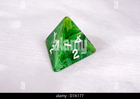 Platonic 4 sided pyramic die against a white background. - Stock Photo