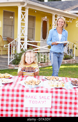 Mother And Daughter Running Charity Bake Sale - Stock Photo