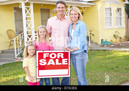 Family Standing By For Sale Sign Outside Home - Stock Photo