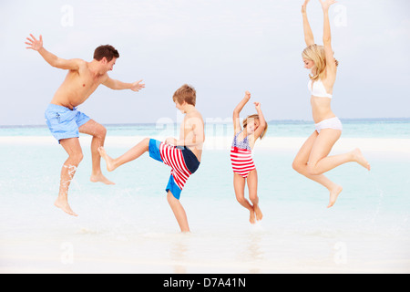 Family Having Fun In Sea On Beach Holiday - Stock Photo