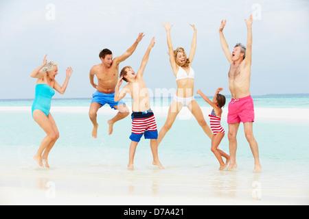 Multi Generation Family Having Fun In Sea On Beach Holiday - Stock Photo