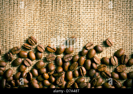 the coffee beans on burlap background - Stock Photo