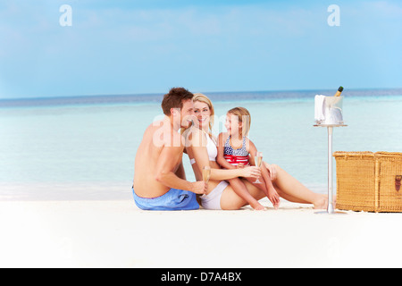 Family On Beach With Luxury Champagne Picnic - Stock Photo
