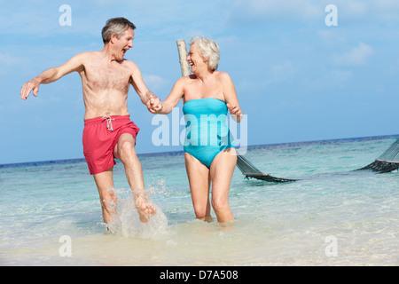 Senior Couple Splashing In Beautiful Tropical Sea - Stock Photo