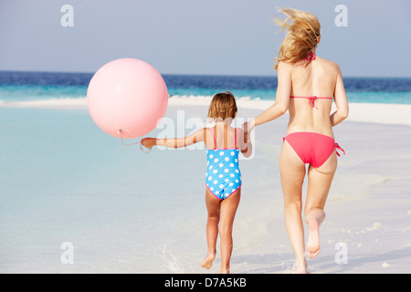 Mother And Daughter Running On Beautiful Beach With Balloon - Stock Photo