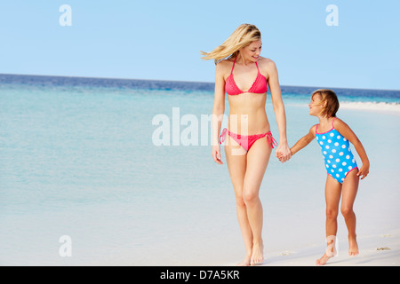 Mother And Daughter Walking On Beautiful Beach - Stock Photo