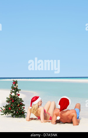 Couple Sitting On Beach With Christmas Tree And Hats - Stock Photo