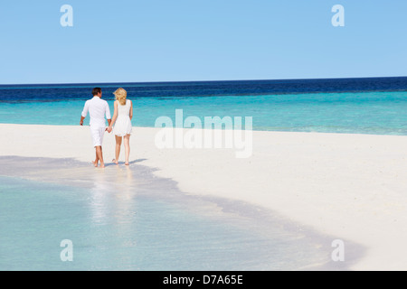 Rear View Of Romantic Couple Walking On Tropical Beach - Stock Photo