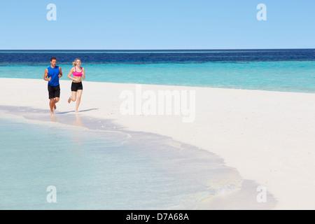 Couple Running On Beautiful Beach - Stock Photo