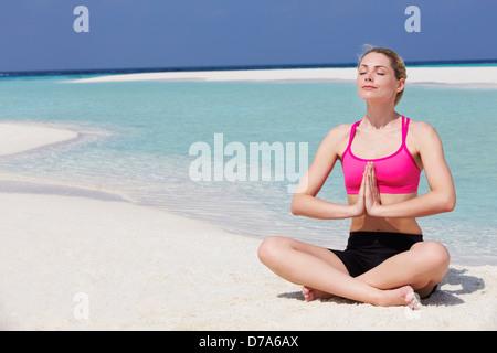 Woman Meditating On Beautiful Beach - Stock Photo