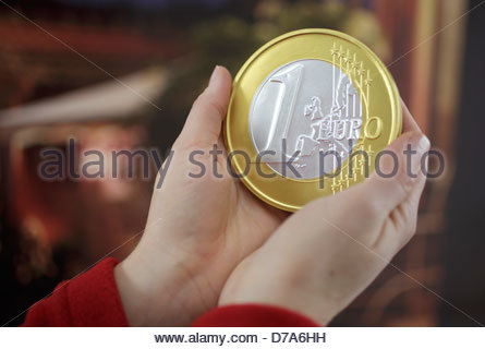 Close-up of a woman holding one euro coin - Stock Photo