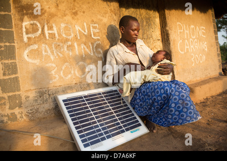 Mother with a solar panel in Lira District, Uganda, East Africa. - Stock Photo