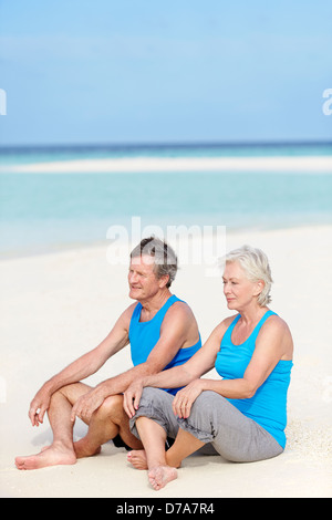 Senior Couple In Sports Clothing Relaxing On Beautiful Beach - Stock Photo
